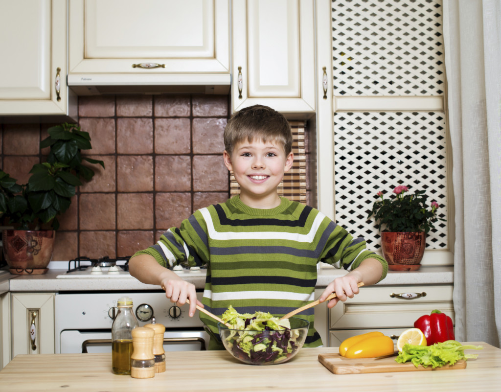 An image of a boy preparing vegetable salad