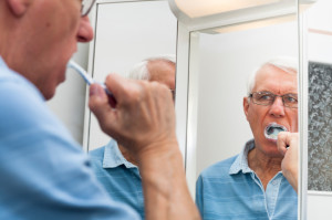 Senior man in mirror brushing his teeth